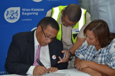Assisted by Neil Zimri of the Department of Agriculture, Minister Meyer registers grain farmer, Alfreda Mars, who farms in  the Swartland District