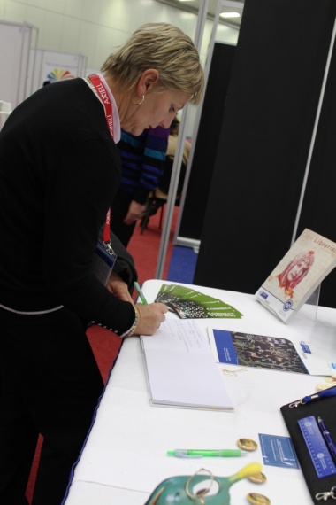 Minister signing the visitors' book at the Western Cape Library Services Exhibition Stand.