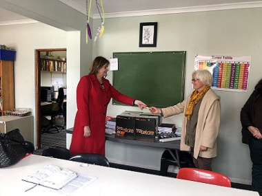 Minister Schafer hands over stationery to the Director of Ons Plek Girls Shelter, Pam Jackson