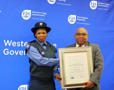 Officer Amanda George receiving her award from Minister Albert Fritz.