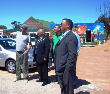 One of the visual artists shows the minister and other dignitaries the new look at Siyabonga Care Village on Friday.