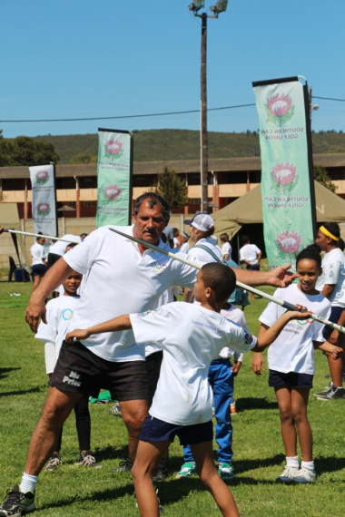 One of the youth being showed how to throw a javelin