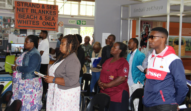 Participants stand to sing Nkosi Sikelel' iAfrika at the start of the Nation Building and Social Cohesion Community Conversations event at the Lwandle Migrant Museum