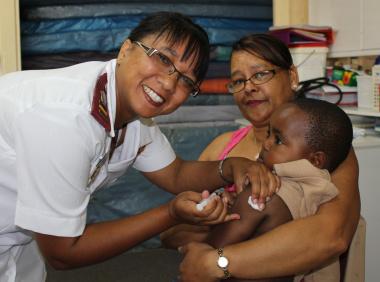 Sr Prudentuia Fillies gives Limyoli GxaGxa his measles shot.