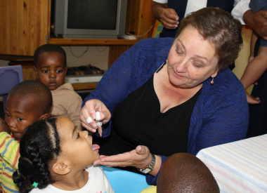 Dr Helise Schumann administers polio drops.