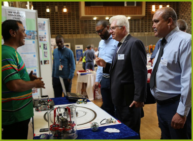 Minister Alan Winde is intrigued by the work done by one of the exhibiting organisations, Helderberg Robotics during the YSRP Programme.
