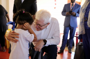 Premier Alan Winde hands over a gift to one of the children who attends Rocklands Educare creche in Mitchells Plain.