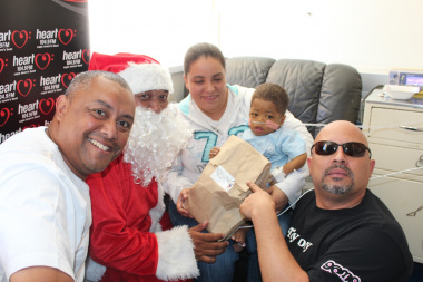 Aden Thomas (Heart 104.9FM), Santa Claus, Toni-Leigh Davies (mom) with Aiden-Lee on her lap and Brandon Leigh (Heart 104.9FM).