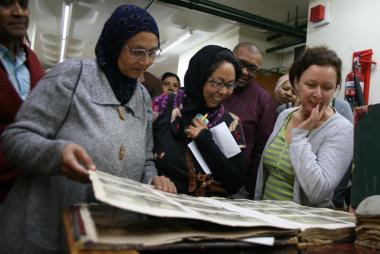Rhodia Davids, Sharita Mia and Roche Stevens admire the archival records together in the Western Cape Archives and Records Service Building.