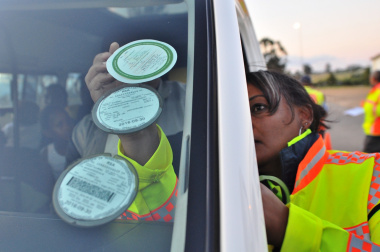Road safety officer Jennifer Solomons places a sticker on a vehicle's windscreen.