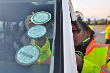 Road safety officer Jennifer Solomons places a sticker on a vehicle's windscreen.