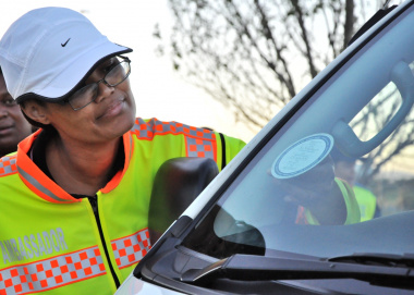 Road safety officer Lizel Plaatjies puts a sticker on a vehicle.