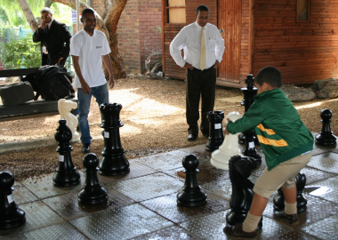 Ryan Daniels makes a move on the giant chess board, while Kenny Solomon and Dr Ivan Meyer look on.