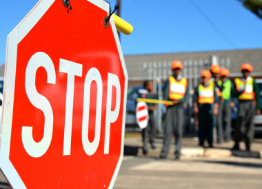 Scholar patrol members regulate traffic slow down vehicles and facilitate safe crossing.