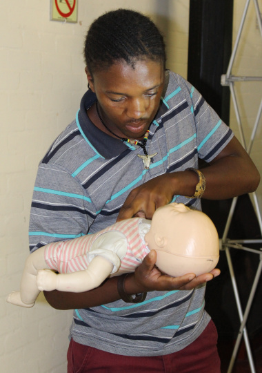 Simphiwe Boya, an initiation carer, demonstrates how to resuscitate a child.