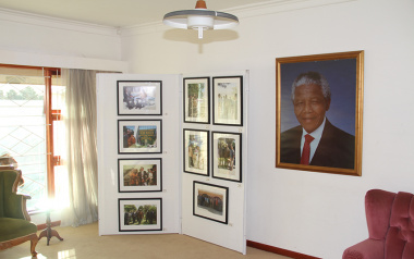 Some photos from the exhibit are seen next to a portrait of president Mandela in the lounge of the house