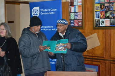 Staff members looking at old editions of the Cape Librarian as part of the historical display