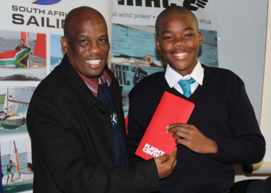 Thabo Tutu from DCAS handing over an airline ticket to Rivaldo Arendse from Du Noon Primary School
