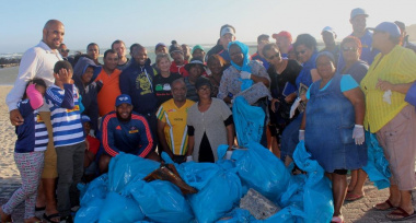The team with the many bags of litter they collected from the beach.