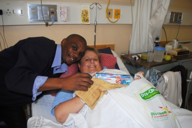 Mr Jemes Rwayi from Dis-Chem Foundation hands a gift bag of toiletries to Ms Denise Knight.