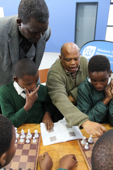 Watu Kobese using the isiXhosa Chess Book to explain chess principles to the learners.