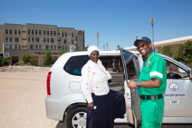 EMS driver Nohani Themelani assists Noluvuyo Mazwayi of Philippi into the new patient transport vehicle.