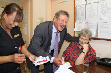 The Western Cape Health Minister, Theuns Botha, shares a light moment during his visit to Zandvlei Care Facility, Macassar, with Sister Mabel van Zyl, Zandvlei Care Facility Manager, and patient Susan Jordaan (64).