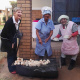 Minister Marais with two locals enjoying griddlecake (roosterkoek)