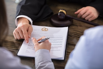 A close up of a female signing a contract with her spouse next to her