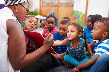 Class listening to teacher reading a story