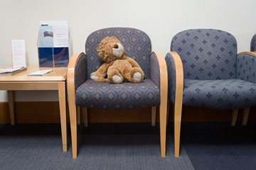 Toy lion teddy bear in a chair at the hospital waiting room
