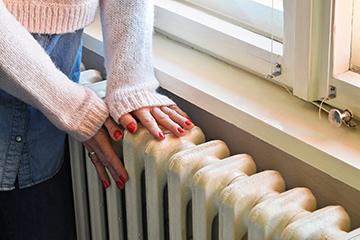 Women warming her hands against wall heater.