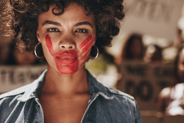 A woman standing with a red hand print across her mouth