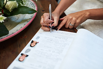 Wife signing marriage contract.