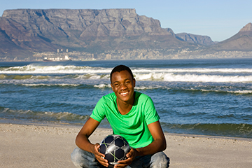Young male with soccer ball on beach