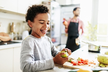 A young boy laughing while he helps his dad prepare lunch by peeling some fruit and veg.