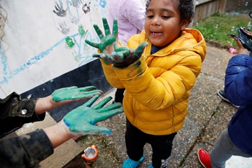 Boy with Autism playing in back yard, making hand prints on the wall, looking at his hands, holding palms up covered in green paint