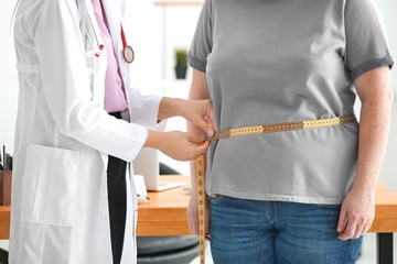 A young female doctor measuring waist of overweight woman with centimeter in clinic